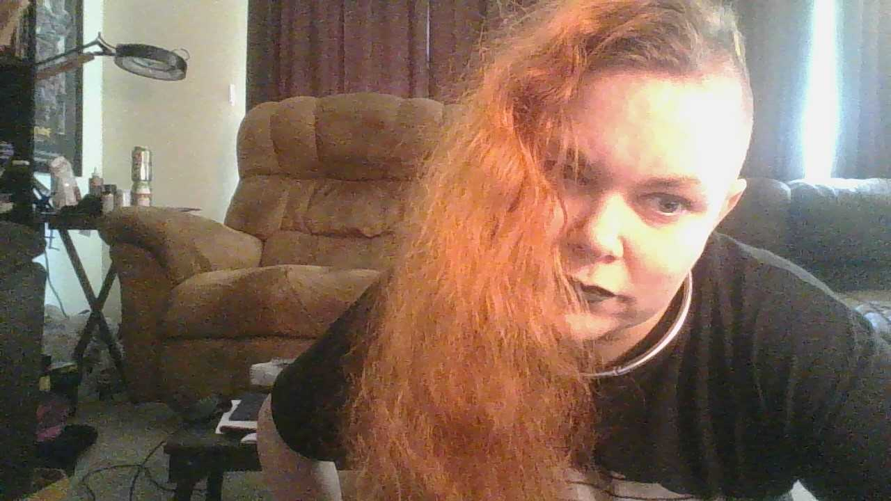 PIcture of person with long orange hair hanging to one side. They are wearing a black shirt. A messy room is behind them.